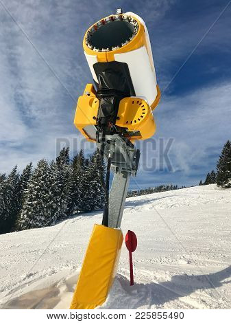 Yellow Snow Maker Machine On Skiing Piste Against Great Blue Sky