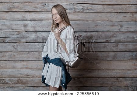 Beautiful girl wearing natural makeup, linen dress. Concept of purity, youth, beautiful skin, posing on pastel wood background, holding a silver backpack on shoulder. poster
