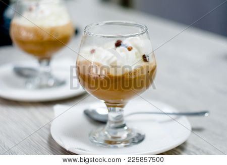 Two Servings Of Fragrant Vanilla-chocolate Ice Cream. Ice Cream With Chocolate Sauce On A Blurry Bac