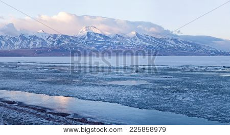 Panorama of holy Rakshas Tal lake under ice and Gurla Mandhata peak in Ngari, Western Tibet, China.