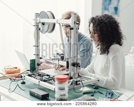 Smiling Students Using A 3d Printer In The School Laboratory, They Are Printing Prototypes, Technolo