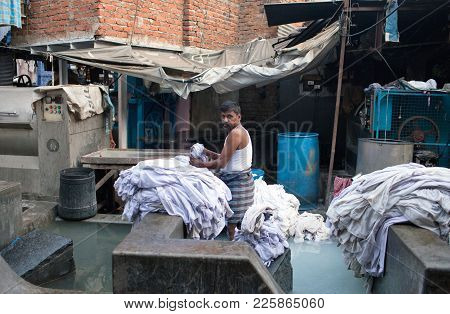 Mumbai, India - January 12, 2016: Indian Worker Washing Clothes At Dhobi Ghat, A Well Know Open Air