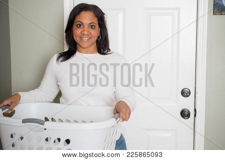 Woman happily doing laundry at her home