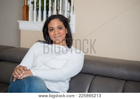 Happy mother at her home sitting on the couch