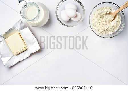 Wheat Flour In The Glass Bowl, Cream In A Glass Jar, Butter, Chicken Eggs - Ingredients For The Doug