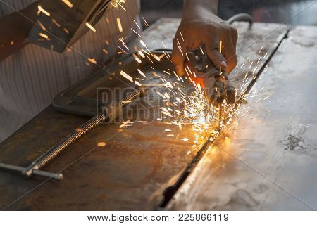 The Worker Welding The Metal Plate By Electric Welding  Process.