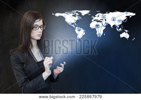 Girl with a tablet in her hands and a connection around the world on the map