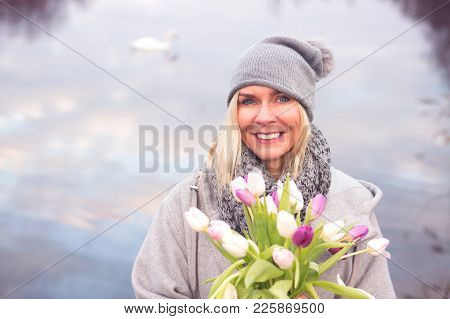 Portrait Of Blond Woman In Front Of Lake With Tulips