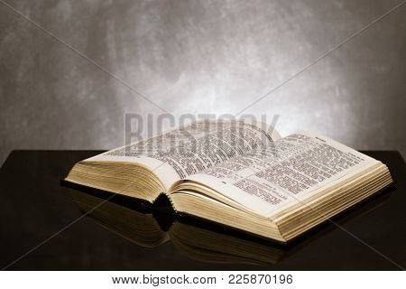 Bible  on a black glass table. Beautiful background.Religion concept.