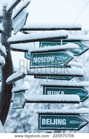 Direction To Different Places Of The World Indicated In A Sign. In The Winter Forest Of Lapland