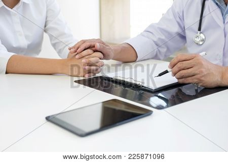Friendly Professional Medical Doctor In White Uniform Coat Holding Patient Hand Sitting At The Desk