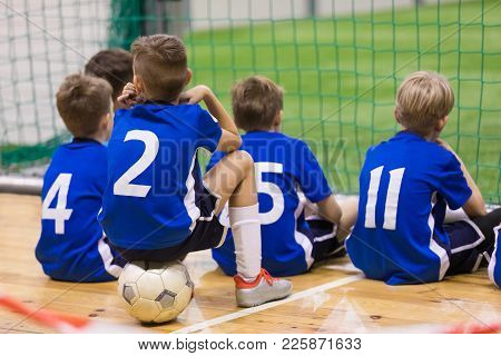 Children Futsal Team. Group Of Young Indoor Soccer Players Sitting Together. Kids School Football To