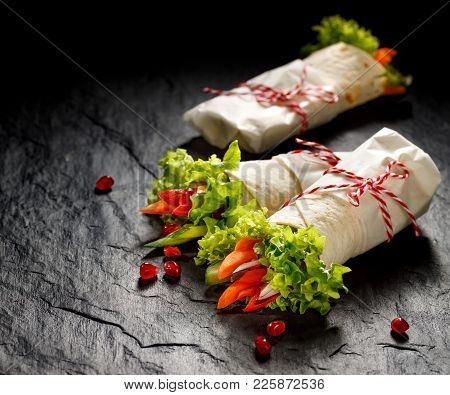 Vegan Tortilla Wraps  Stuffed With Hummus And Fresh Vegetables On A Black Stone Background