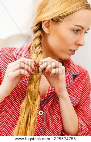 Fancy Trendy Blond Hairstyle At Home Concept. Woman Wearing Pink Pajamas Doing Braid On Blonde Hair