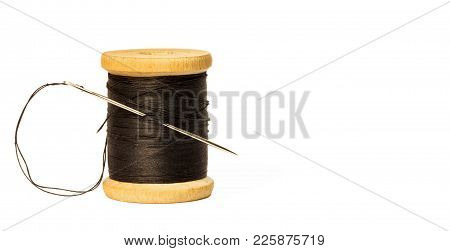 sewing needle with black thread stuck in wooden spool with black threads close up isolated on white background poster