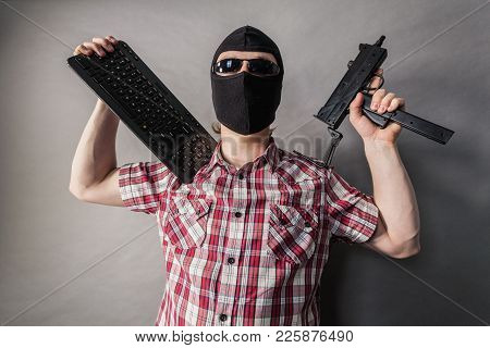 Crazy Hacker Man. Unrecognizable Guy Wearing Black Balaclava Holding Gun And Keyboard. Hate Speech O