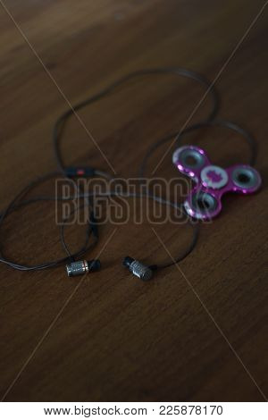 Close Up Top View Photo Of Headphones And Modern And Hot Toy Fidget Spinner