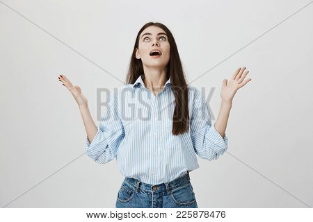 Relieved And Gladful Young European Female Raising Hands And Looking Up With Opened Mouth And Satisf