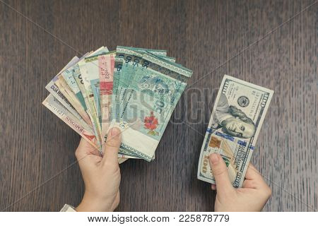 Female hand with money of south-east Asia. Currency of Hong Kong, Indonesia, Malaysia, Thai, Singapo