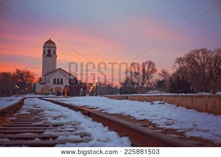 sunrise photo of the boise train depot and the railroad tracks covered in snow with a flock of geese flying in the morning light on a cold winter day toned with a retro vintage instagram filter