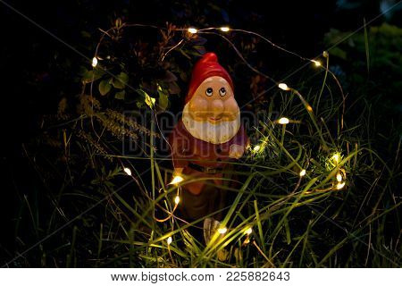 Garden Gnome And Lights In The Evening In The Grass