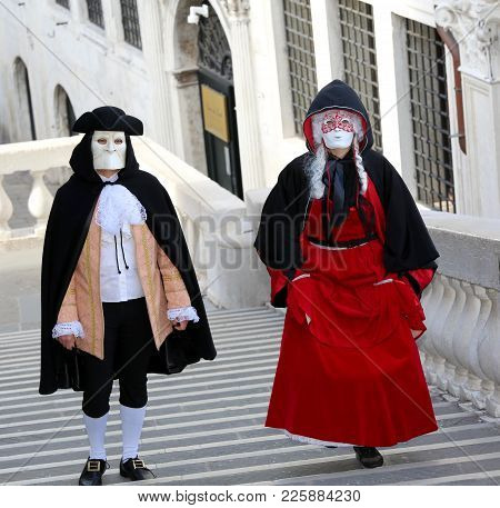 Venice, Italy - February 5, 2018: A Couple Of Masked Lovers Walk On The Steps Of The Famous Rialto B