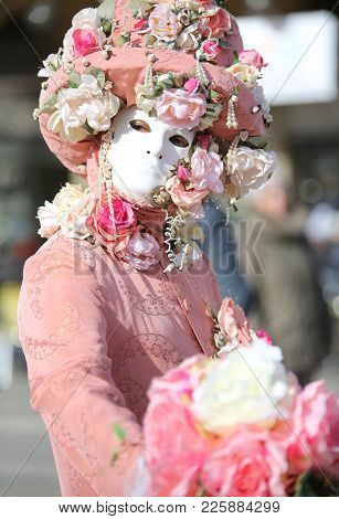 Venice, Italy - February 5, 2018: Carnival Mask And A Big Bouquet Of Rose Flower In Hand