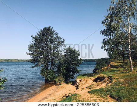 Summer Day On The River. Calm Expanse Of Water, Sandy Shore, Green Trees. On The Other Side Dense Fo
