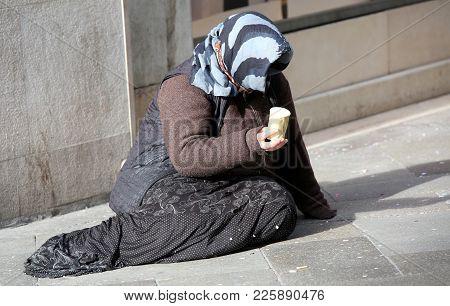 Elderly Poor Gypsy Woman Begs For Alms On A European Road