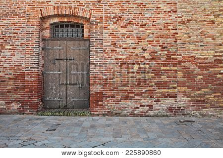 Retro Background With Old Brick Wall, Stone Paved Sidewalk And Ancient Wooden Door With Bolts