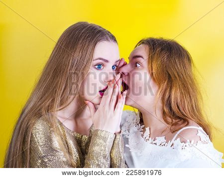 Young Girl Telling Her Best Friend Private Secret. Girlfriend Listening With Surprised Expression On
