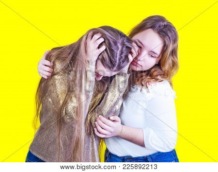 Troubled Young Girl Comforted By Her Friend. Isolated On Light Background