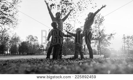 Young Family Playing With Autumn Leaves Standing In A Circle In A Rural Field Tossing Them Into The