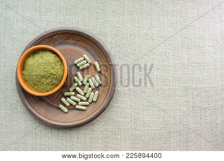 Supplement Kratom Green Capsules And Powder On Brown Plate. Herbal Product Alt-medicine Kratom Is  O
