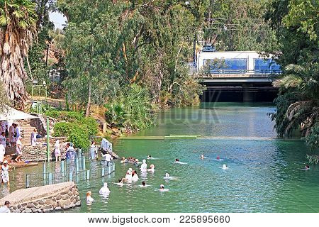 Tiberias, Israel - September 21, 2014: Pilgrims In White Robes Plunge At The Jordan River (yardenit)
