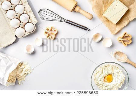Baking Ingredients For Pastry On The White Table. Ingredients For The Dough: Flour, Eggs, Butter. To