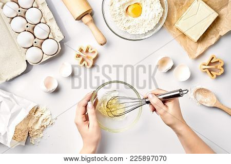 Female Chef Whisking Eggs In Glass Bowl On Kitchen Table. Ingredients For The Dough: Flour, Eggs, Bu