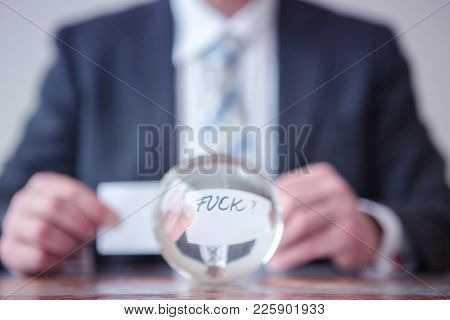 Closeup Of Man Holding Paper With Word Fuck In Front Of Glass Ball