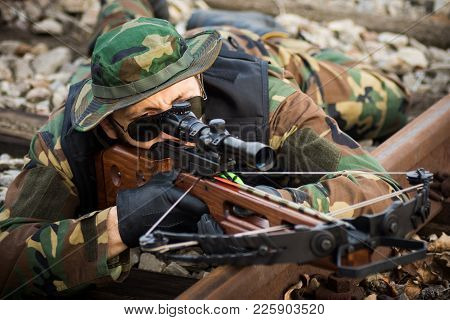 The Military Man Is Aiming With Crossbow Weapon And Lying Down On Railway Track.
