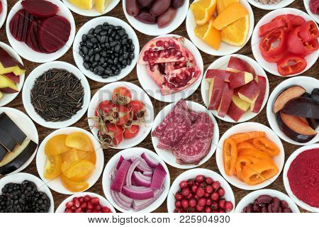 Anthocyanin super health food selection in porcelain bowls on rustic wood background. Also high in antioxidants, vitamins and minerals. hHealty superfood concept.