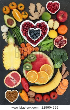 Healthy super food collection with fresh fruit, vegetables, nuts, pollen grain, herbs and spices with foods high in antioxidants, anthocyanins, fibre, omega 3, minerals and vitamins. Top view on slate