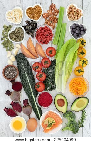 Brain boosting health food concept  with fish, vegetables, seeds, nuts, berry fruit, herbs and pollen grain. Foods high in omega 3, vitamins, minerals, antioxidants and anthocyanins. Top view.