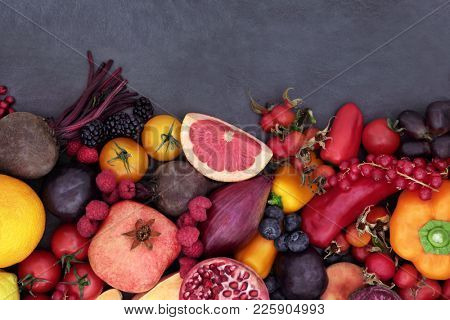 Healthy eating super food background border with fruit and vegetables high in anthocyanins, antioxidants, minerals and vitamins on slate.