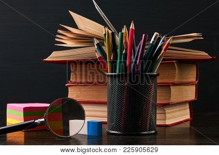 Books On The Desk In The Auditorium With Blackboard On Background With Copy Space. School Equipment