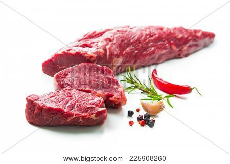 Fresh and raw beef meat. Whole piece of tenderloin with steaks and spices ready to cook isolated on white background