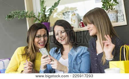 Three Beautiful Girls Sit And Use A Smartphone