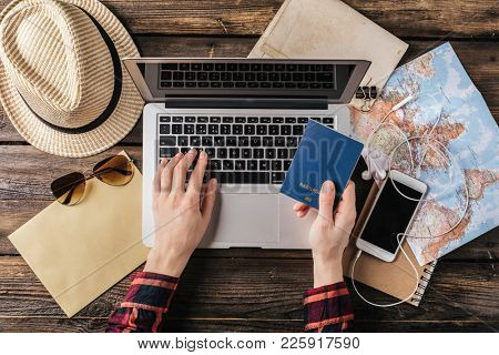 Female hand holding a passport over a laptop. Planning a trip, buying tickets online. Top view