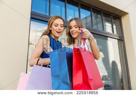 sale, consumerism and people concept - happy young women looking into shopping bags outdoors