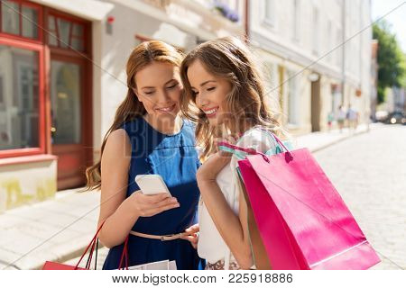 technology, sale, consumerism and people concept - happy young women with shopping bags and smartphone on city street
