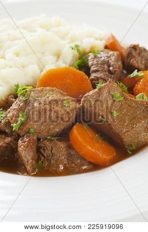 A Simple Plate Of Stew With Carrots, Served With Mashed Potato.